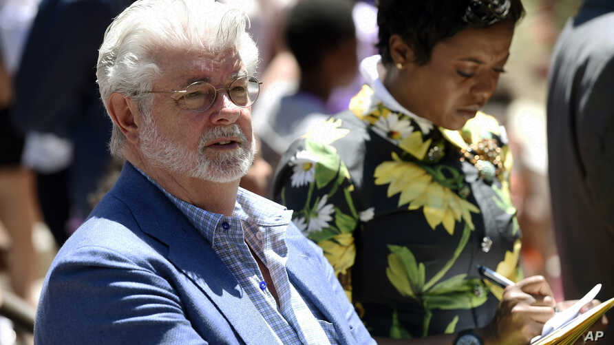 Filmmaker George Lucas, left, and his wife, Mellody Hobson, listen to remarks at a news conference outside Los Angeles City Hall, June 27, 2017. The Los Angeles City Council approved preliminary steps that will allow construction of the $1.5 billion