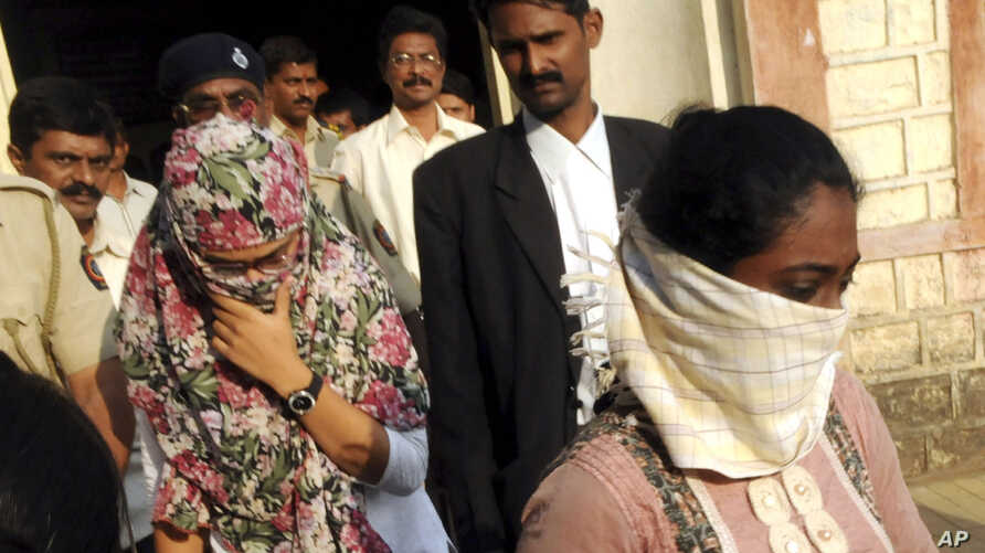 Face covered Shaheen Dhada, left, and Renu Srinivas, come out of a court in Mumbai, India after being arrested for their Facebook post, November 20, 2012.