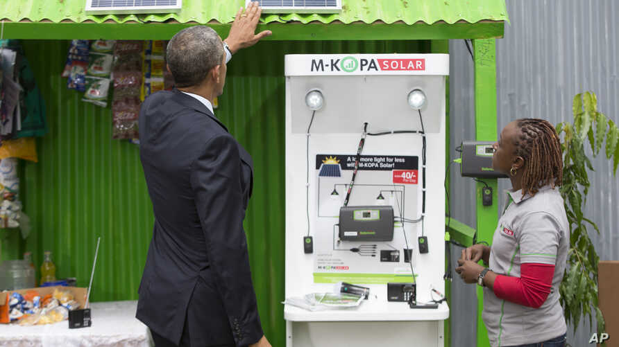 President Barack Obama looks at a solar power exhibit during a tour of the Power Africa Innovation Fair, Saturday, July 25, 2015, in Nairobi, Kenya. In Nigeria, Lumos Global is among the firms rolling out solar power technology. The company received