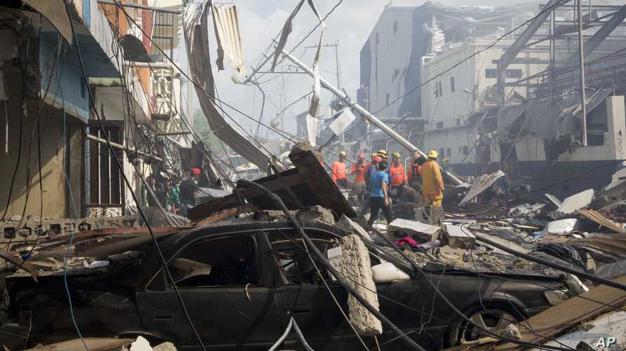 Search and rescue personnel stand in the debris caused by an explosion at the Polyplas plant in the Villas Agricolas neighborhood in Santo Domingo, Dominican Republic, Dec. 5, 2018.