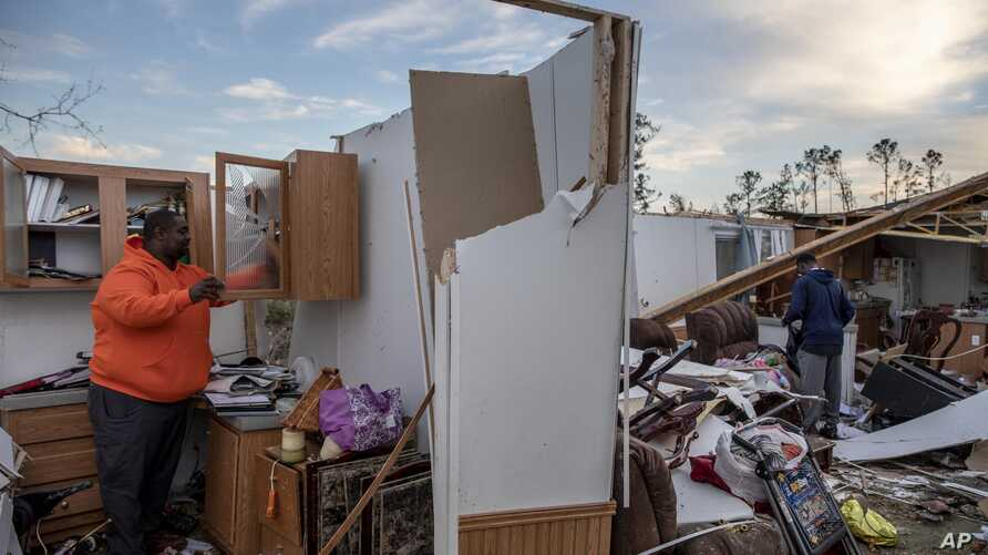 FILE - Granadas Baker, left, and son Granadas Jr., 18, right, retrieve personal items from the damaged home where they survived a tornado a day earlier in Beauregard, Ala., March 4, 2019.
