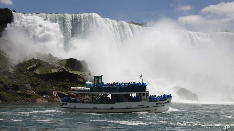 FILE - Tourists ride the Maid of the Mist tour boat at the base of the American Falls in Niagara Falls, New York, June 11, 2010.
