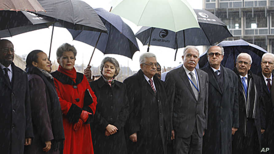 Palestinian President Mahmoud Abbas, center, stands on a podium with UNESCO director general Irina Bokova, fourth from left, and other UNESCO and Palestine government officials in Paris, December 13, 2011.
