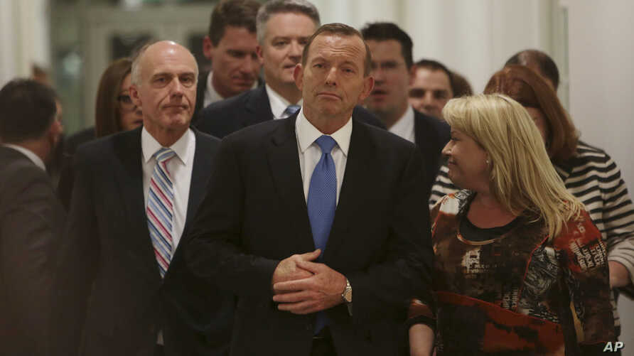 Australian Prime Minister Tony Abbott, center, leaves the Australian Liberal Party meeting in which he lost the party leadership at Parliament House in Canberra, Monday, Sept. 14, 2015.