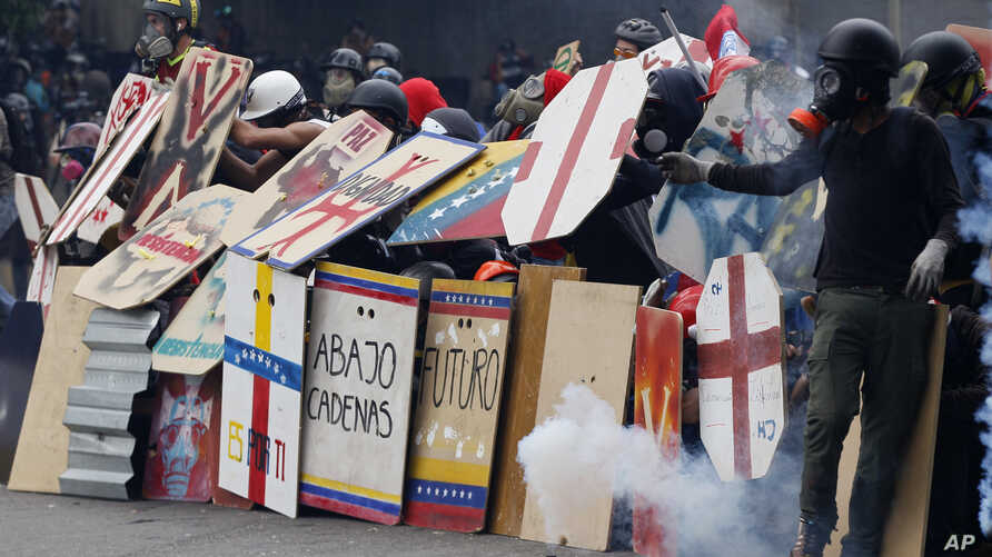 Anti-government protesters using handmade shields face off with security forces blocking a student march from reaching the Education Ministry in Caracas, Venezuela, May 8, 2017.