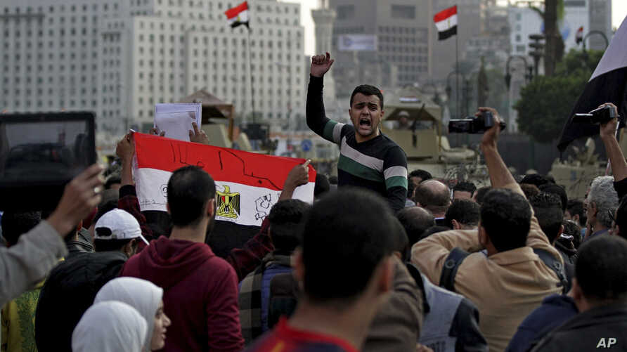 "Protesters shout anti-government slogans and hold a national flag with ""God is great written on it,"" after a judge on Saturday dismissed the case against former President Hosni Mubarak, Nov. 29, 2014."