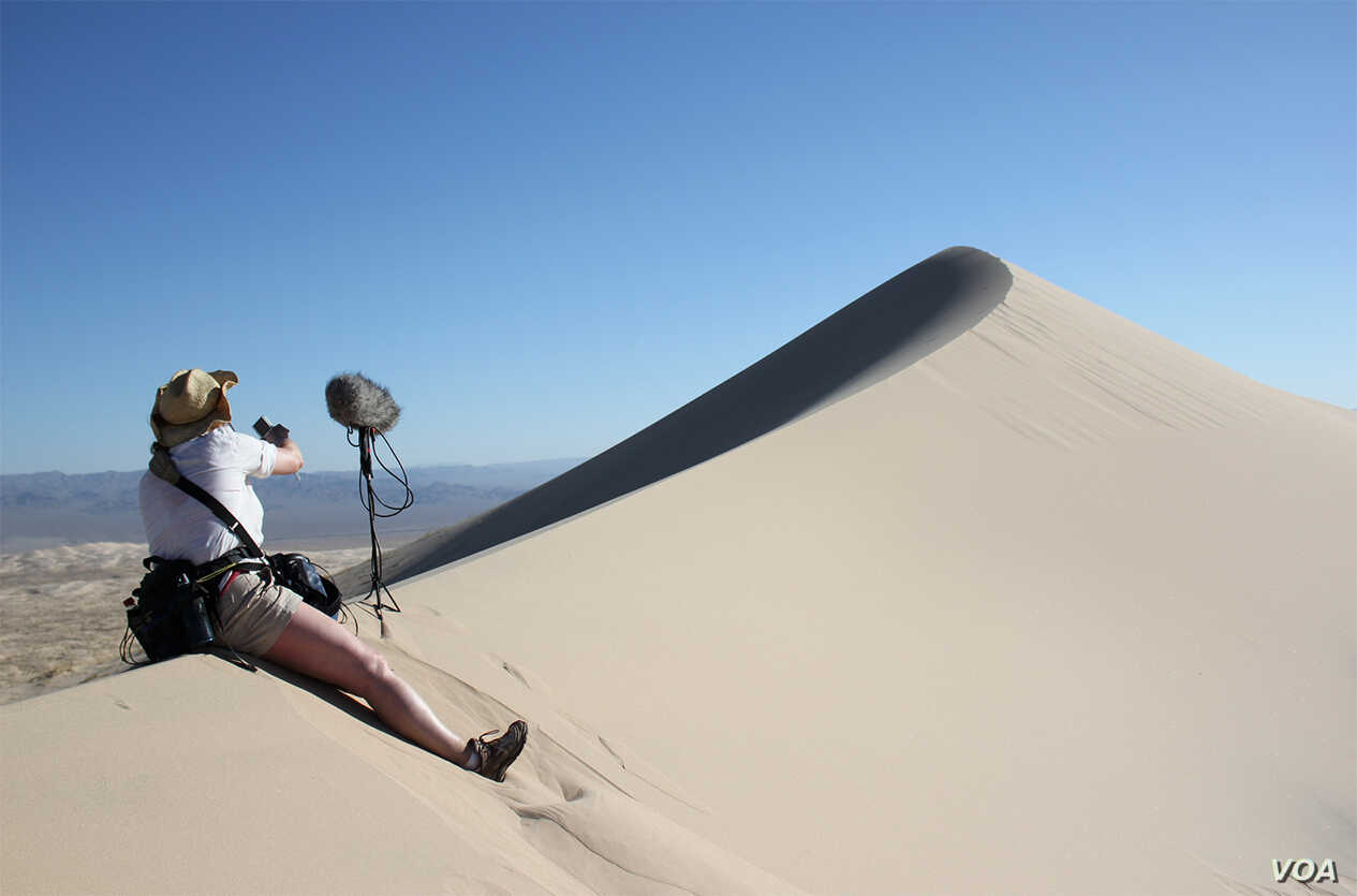 A sound engineer sets up to record the singing sand dunes in the Mohave Desert, California.  (Trevor Cox)