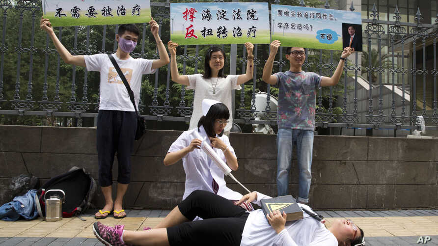 FILE - Gay rights campaigners act out electric shock treatment to protest outside a court where the first court case in China involving so-called conversion therapy is held in Beijing, China, July 31, 2014.