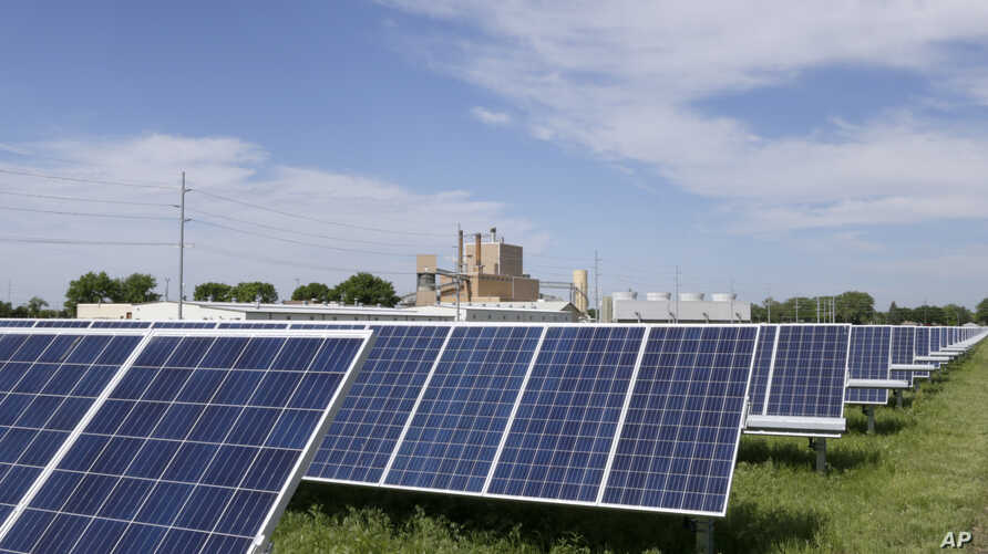 A solar panel array collects sunlight with the Fremont, Neb., power plant seen behind it, May 31, 2018. Solar energy is gaining traction in a small but growing number of Nebraska cities, but the technology still faces a number of obstacles that is ke