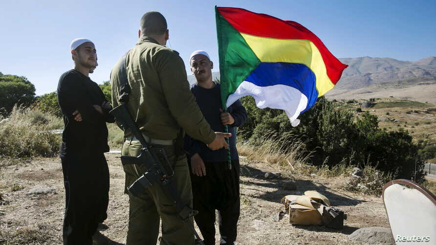 A member of the Druze community holds a Druze flag as he speaks to an Israeli soldier near the border fence between Syria and the Israeli-occupied Golan Heights, near Majdal Shams, June 18, 2015..
