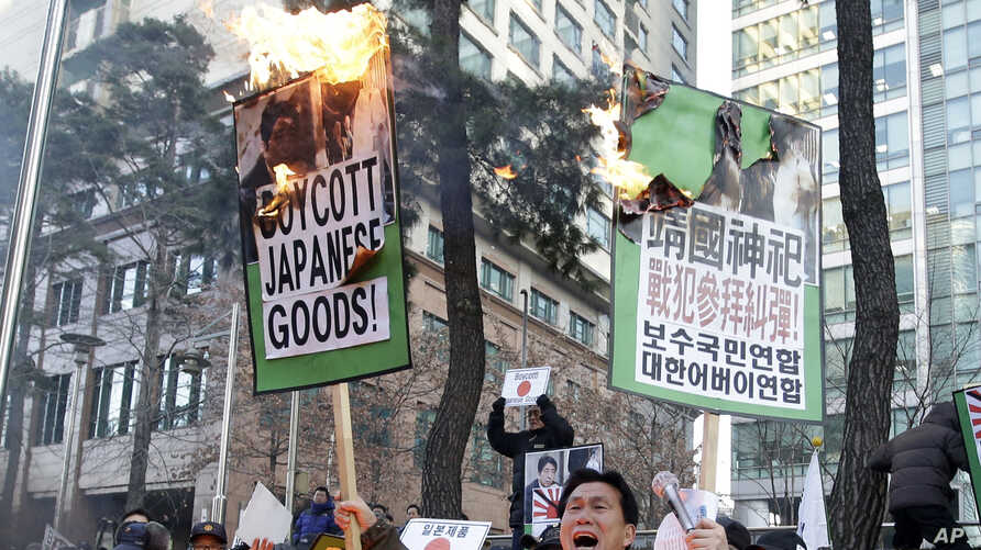 A South Korean protester holds burning placards during a rally against Japanese Prime Minister Shinzo Abe in front of the Japanese Embassy in Seoul, South Korea, Friday, Dec. 27, 2013.