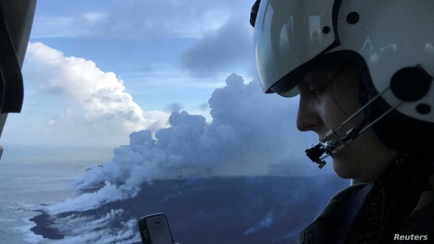 Dr. Jessica Ball of USGS, a geologist and volcanologist who does research at the US Geological Survey, is updating Hawaiian Volcano Observatory scientists on the ground during a helicopter overflight of the ocean entry of the fissure 8 lava flow wher