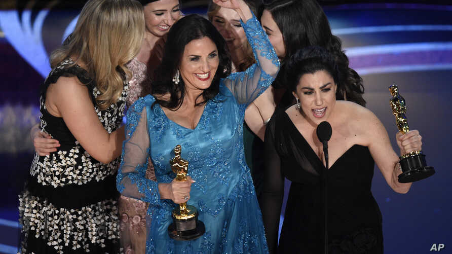 """Melissa Berton, center left, and Rayka Zehtabchi accept the award for best documentary short subject for """"Period. End of Sentence."""" at the Oscars on Sunday, Feb. 24, 2019, at the Dolby Theatre in Los Angeles."""