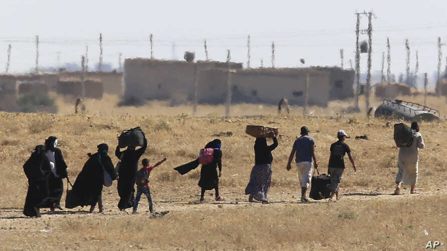 A picture taken from the Turkish side of the border shows Syrian refugees on the Syrian side of the border retreating further inland after waiting for several hours to cross the border into Turkey, near Akcakale, Sanliurfa province, southeastern Turk