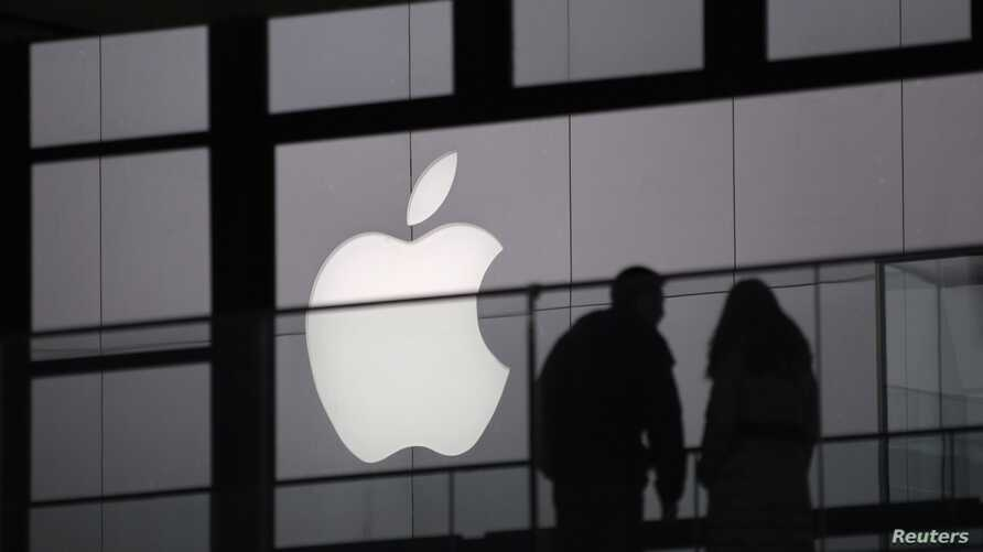 People walk past the Apple logo near an Apple Store at a shopping area in central Beijing, February 19, 2013