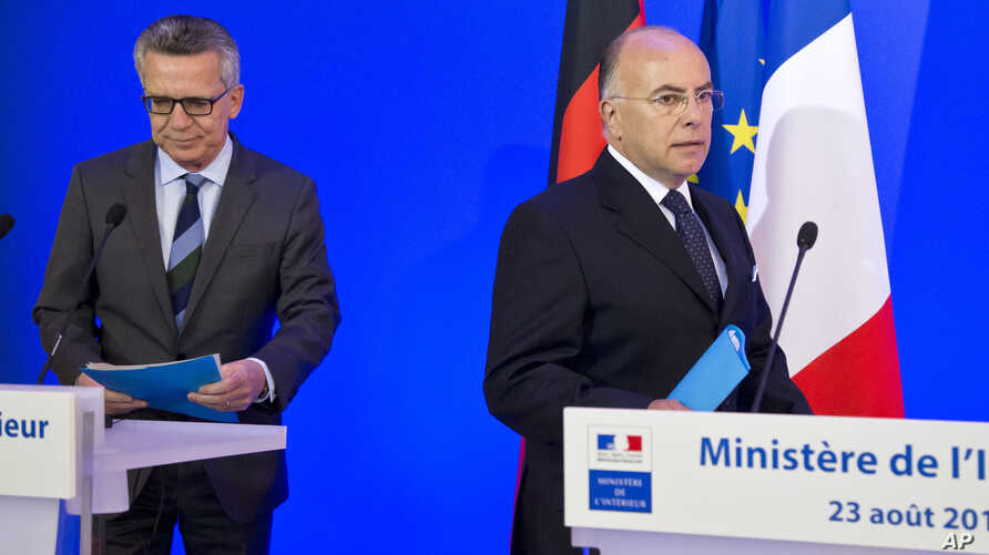 German Interior Minister Thomas de Maiziere, left, and French Interior Minister Bernard Cazeneuve arrive for a joint media conference in Paris, Aug. 23, 2016.