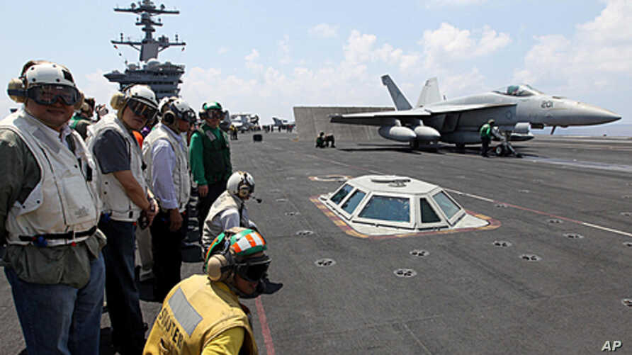 Philippine President Benigno Aquino III (2nd L) watches an F/A-18 Hornet fighter jet about to be catapulted from the US Navy's USS Carl Vinson aircraft carrier near the Philippines, May 14, 2011