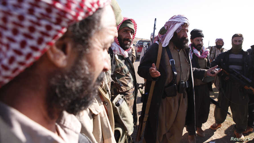 FILE - Yazidi fighters gather on the summit of Mount Sinjar as they head to battle Islamic State militants, in Iraq, Dec. 21, 2014. IS swept into Sinjar town and surrounding villages in early August; many residents were from the Yazidi religious comm