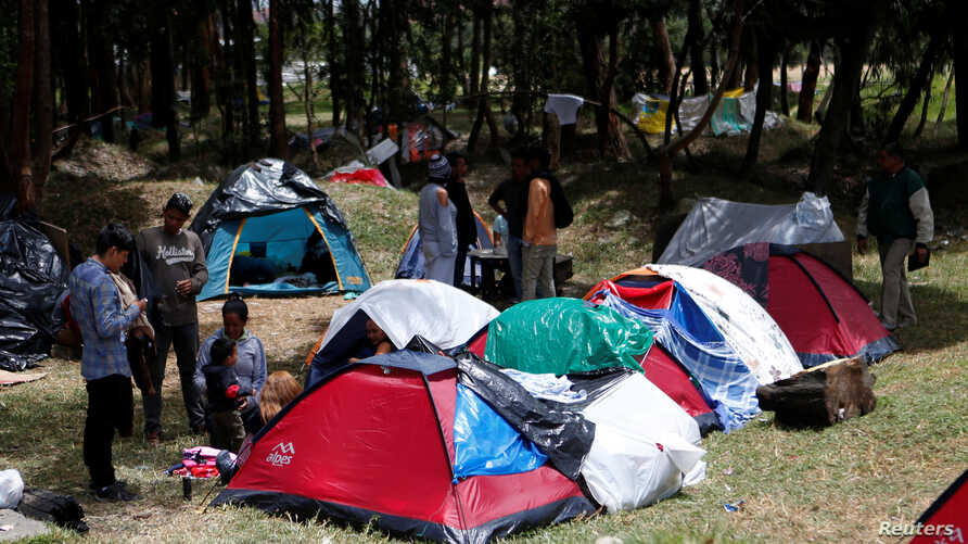 Venezuelan migrants stand at a makeshift camp near the transport terminal in Bogota, Colombia, Sept. 5, 2018.