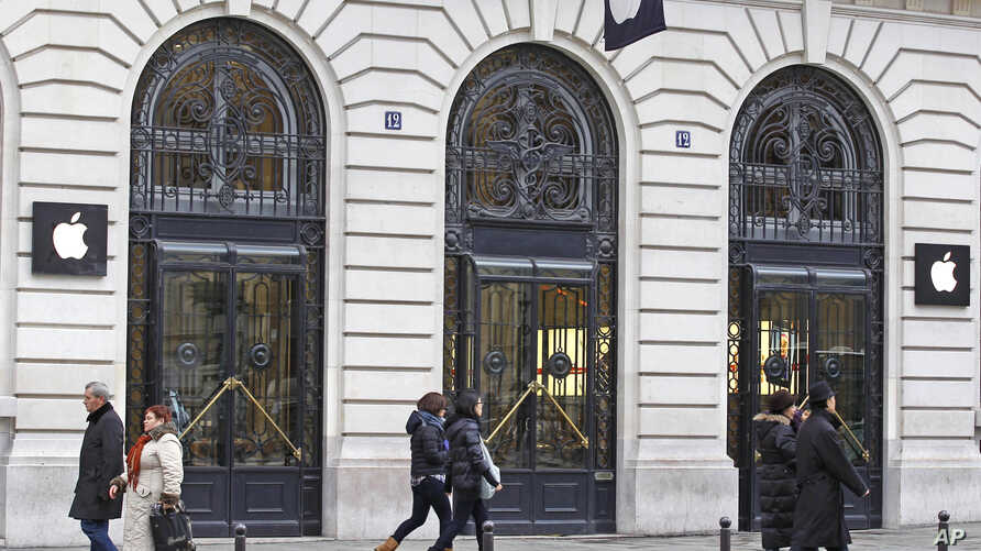 FILE - In this Jan. 1, 2013 file photo, Parisians and tourists wander in front of an Apple store in Paris. A French prosecutor office said Jan. 9, 2018 an investigation into Apple over alleged planned obsolescence of some of its smartphones has been