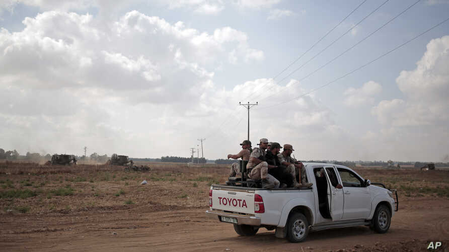 FILE - In this June 10, 2015 photo, Palestinian Hamas gunmen ride on the back of a pick-up truck as they patrol the border with Israel near the southern Gaza Strip town of Khan Younis, as Israeli military bulldozers are seen in the background.