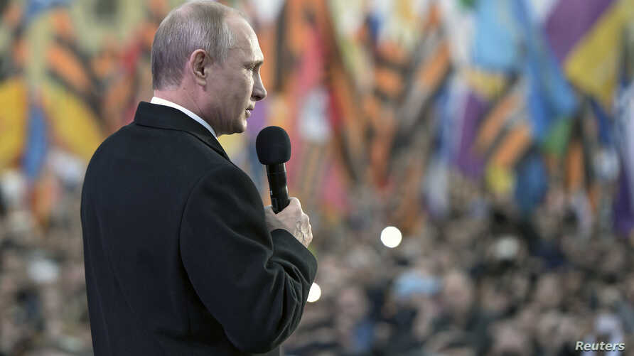 Russian President Vladimir Putin addresses the audience during a festive concert marking the first anniversary of the Crimean treaty signing, with St. Basil's Cathedral seen in the background, in central Moscow, March 18, 2015.