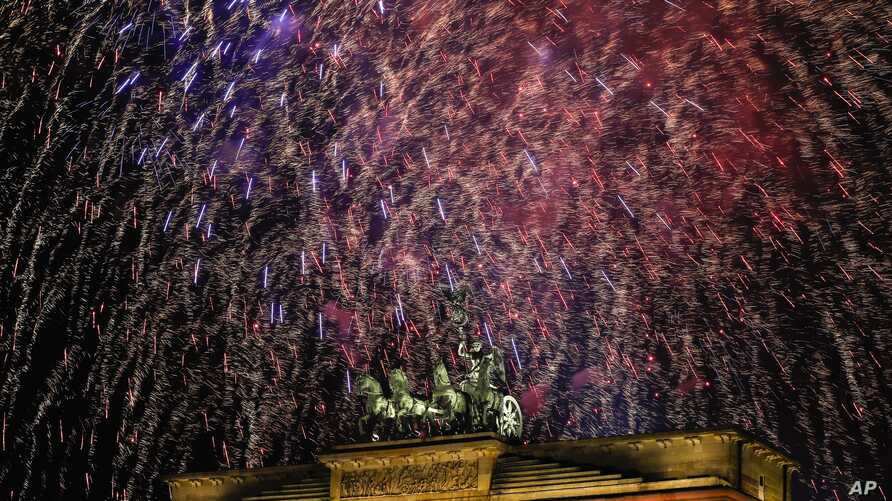 Fireworks light the sky above the Quadriga at the Brandenburg Gate during New Year's celebrations shortly after midnight in Berlin, Jan. 1, 2018.