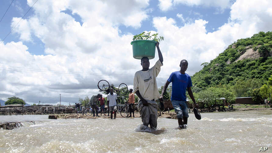 People cross a river with their belongings where a bridge once stood in Phaloni, Southern Malawi, Jan 22, 2015.