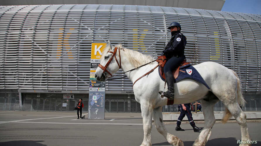 FILE - A French policeman patrols on a horse during a mock chemical attack drill at the Pierre Mauroy stadium in Villeneuve d'Ascq, France, April 21, 2016, in preparation of security measures for the 2016 European football championship.