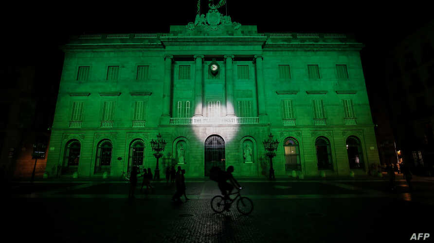 FILE - The City Hall of Barcelona is illuminated in green in support of the Paris climate accord aiming to meet greenhouse gas emission targets, in Barcelona, Spain, June 2, 2017.