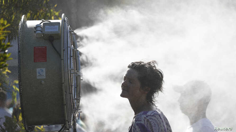 A supporter cools down herself after the match between Britain's Daniel Evans and Japan's Tatsuma Ito.