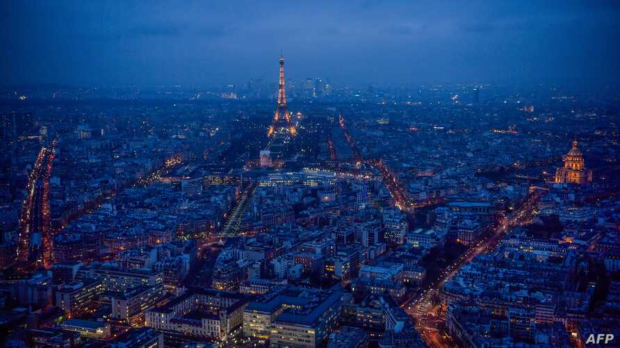 This general view taken from the rooftop of The Tour Montparnasse at twilight on January 8, 2018, shows The Eiffel Tower (C) and The Dome des Invalides (R) in Paris.
