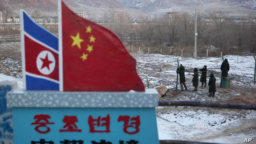 "FILE - A Chinese-built fence near a concrete marker depicting the North Korean and Chinese national flags with the words ""China North Korea Border"" at a crossing in the Chinese border town of Tumen in eastern China's Jilin province."