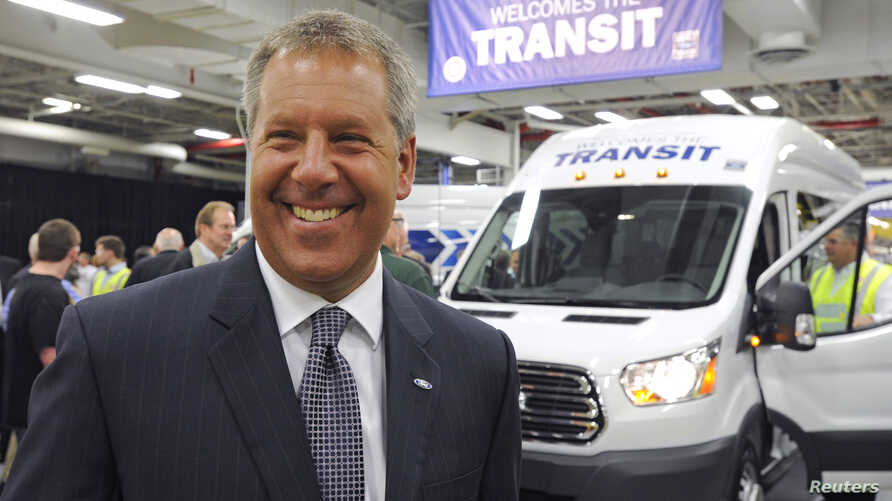 FILE - Joe Hinrichs, Ford president of The Americas, celebrates after driving the first Ford Transit Van from the assembly line at a Ford plant in Claycomo, Missouri, on Apr. 30, 2014.