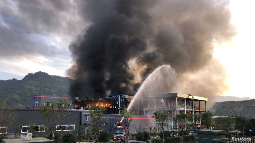Rescue workers try to put out a fire after an explosion at a chemical plant inside an industrial park in Yibin, Sichuan province, China, July 12, 2018.