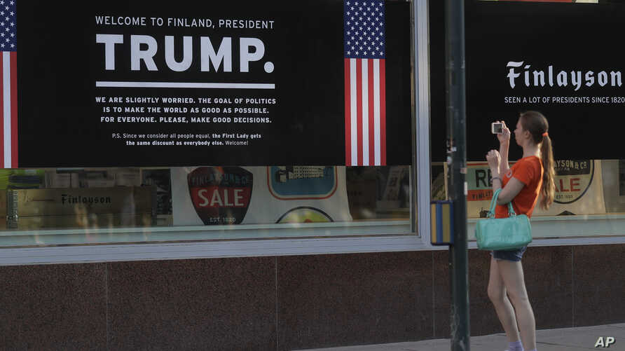A woman takes a picture of a poster welcoming U.S. President Donald Trump and Russian President Vladimir Putin at a store in downtown Helsinki, July 14, 2018. Trump and Putin will meet Monday at Finnish presidential palace in Helsinki.