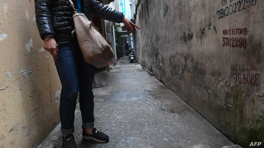 FILE - This photo, taken March 15, 2017, shows a mother pointing to the place where her eight-year-old daughter was molested by a family friend in a residential quarter of Hanoi, Vietnam.