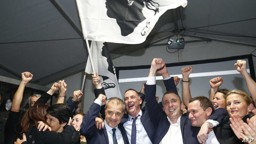 Candidates for the Pe a Corsica nationalist party Jean Guy Talamoni (4L) and Gilles Simeoni (5L) celebrate with party members and supporters after the announcement of the results in the territorial elections in Bastia on the French Mediterranean Isla