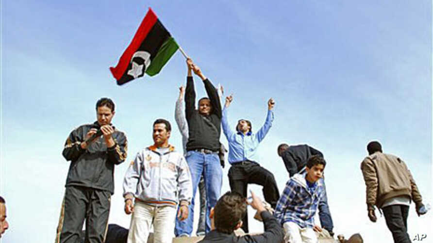 Residents stand on a tank holding a pre-Gadhafi era national flag inside a security forces compound in Benghazi, Libya, February 21, 2011