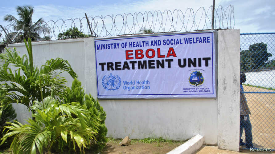 A man stands at the gate of an Ebola virus treatment center in Monrovia, Sept. 21, 2014.
