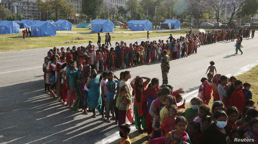 Women queue for food supplies at a camp for displaced earthquake victims in Kathmandu, Nepal, May 5, 2015. REUTERS/Olivia Harris