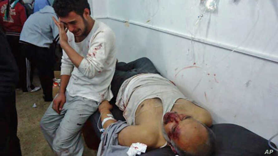 Wounded men are seen in the Sunni Muslim district of Baba Amr in Homs, Syria, February 8, 2012.