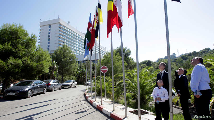 People look at flags ahead of  the OPEC Ministerial Monitoring Committee in Algiers, Algeria, Sept. 22, 2018.