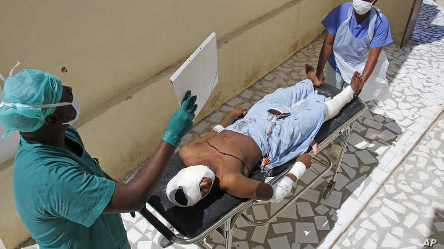 Medical workers attend to a man injured in a mortar shell attack, at Medina hospital during Somali Independence day ceremony in Mogadishu, Somalia, July 1, 2018.