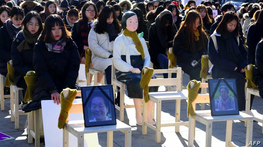 "People sit around a statue of a ""comfort woman"" during an installation of empty chairs during a performance event, commemorating the death of eight former sex slaves this year, in Seoul, South Korea."