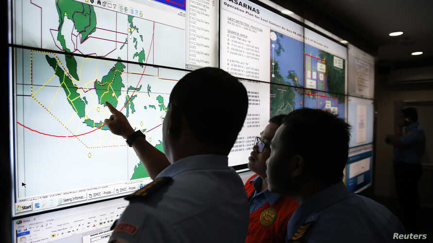 Military and rescue authorities monitor progress in the search for AirAsia Flight QZ8501 inside the National Search and Rescue Agency in Jakarta  December 29, 2014.