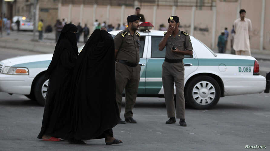 FILE - Women walk past members of Saudi security forces on patrol in Manfouha, southern Riyadh, Saudi Arabia, Nov. 14, 2013.