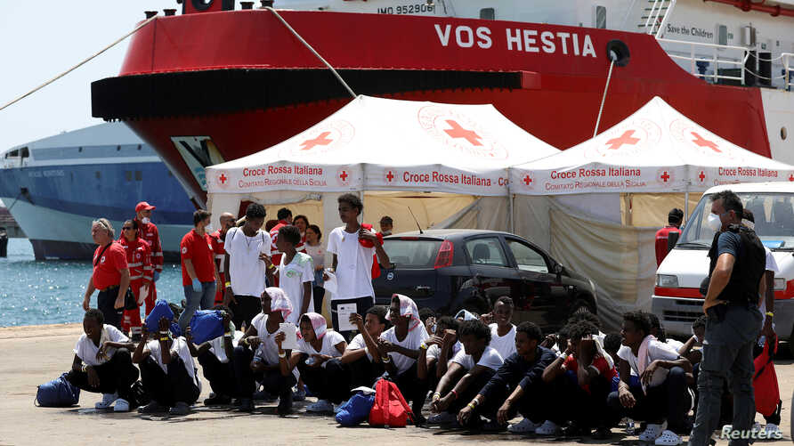 """Migrants sit on the ground after disembarking from Vos Hestia ship of NGO """"Save the Children"""" in the Sicilian harbour of Augusta, Italy, Aug. 4, 2017."""