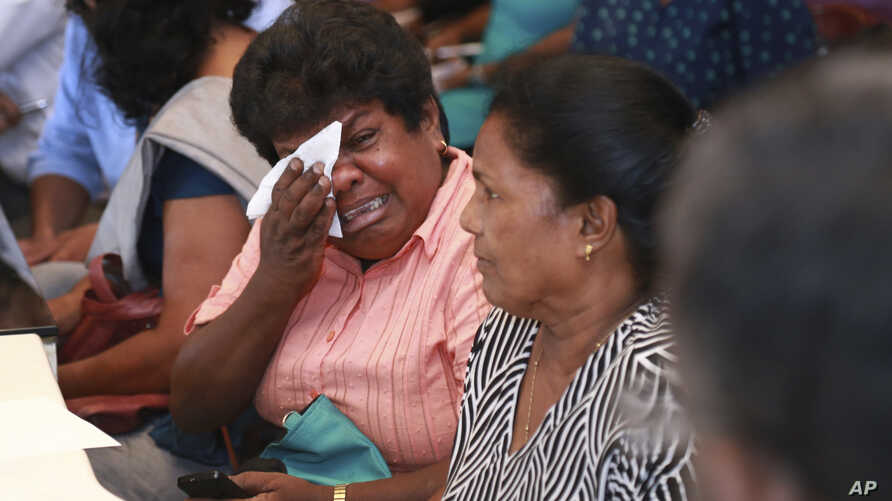 Samudra Bulathasinhala, in pink, a relative of a crew member captured by Somali pirates, cries during a meeting with Sri Lankan shipping authorities in Colombo, Sri Lanka, March 16, 2017.