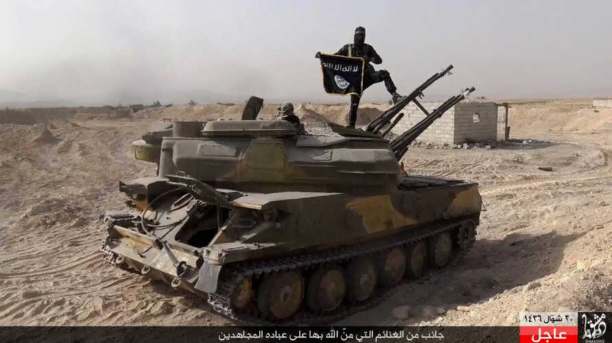 FILE - An Islamic State militant holds the group's flag as he stands on a tank captured from Syrian government forces, in the town of al-Qaryatayn southwest of Palmyra, central Syria.